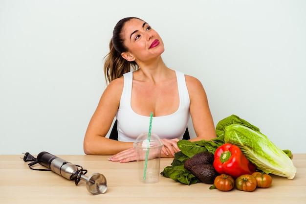 Jovem mulher caucasiana preparando um smoothie saudável com vegetais, sonhando em atingir seus objetivos