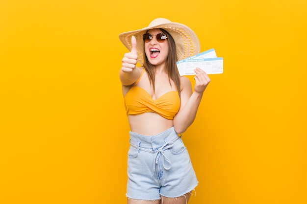 Jovem mulher caucasiana pronta para ir à praia com bilhetes aéreos