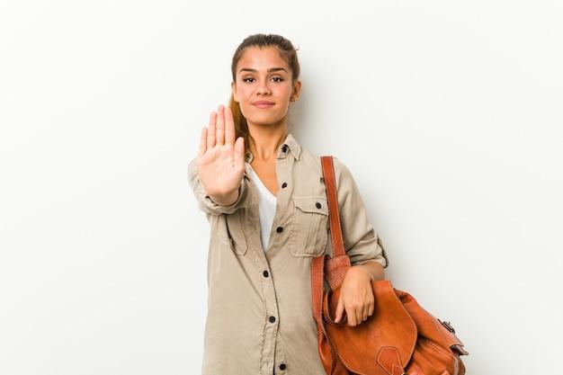 Jovem mulher caucasiana, pronta para uma viagem em pé com a mão estendida, mostrando o sinal de stop, impedindo-o.