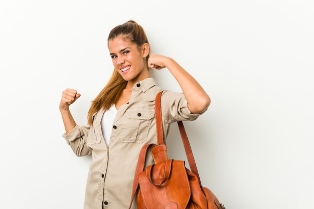 Jovem mulher caucasiana, pronta para uma viagem, levantando o punho após uma vitória, o conceito de vencedor.
