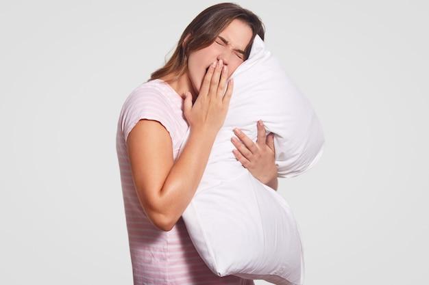 Jovem mulher caucasiana quer dormir, mantém a mão na boca, vestida com roupas casuais, mantém o travesseiro, tem expressão cansada, isolada no branco. manhã e conceito de despertar