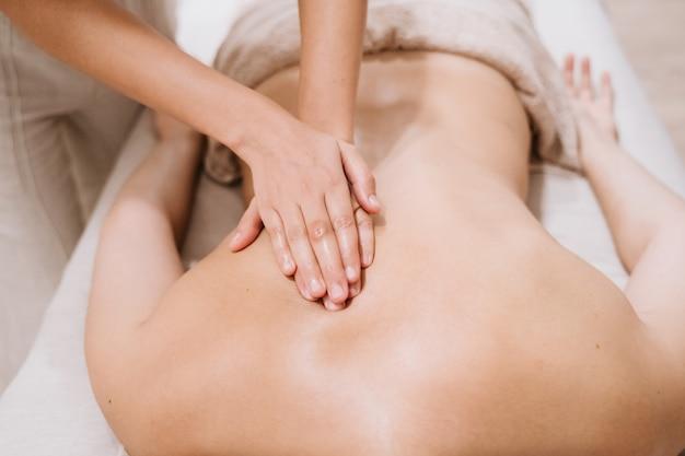 Jovem mulher caucasiana, recebendo massagem nas costas da fisioterapeuta fêmea na clínica. conceito de fisioterapia