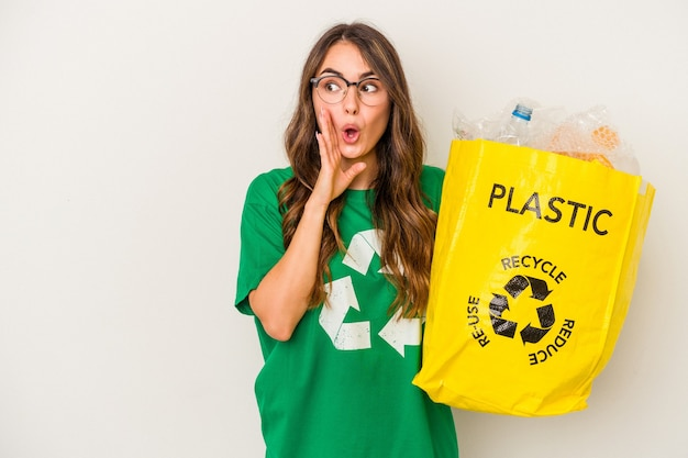 Jovem mulher caucasiana, reciclando um cheio de plástico isolado no fundo branco, está contando uma notícia secreta da frenagem e olhando para o lado