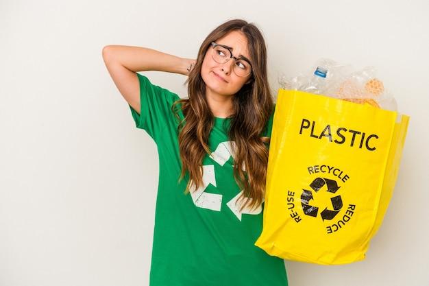 Jovem mulher caucasiana, reciclando um cheio de plástico isolado no fundo branco, tocando a nuca, pensando e fazendo uma escolha.