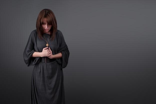 Jovem mulher caucasiana, rezando em fundo preto