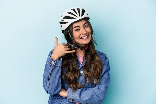 Jovem mulher caucasiana rinding uma bicicleta isolada em um fundo azul, mostrando um gesto de chamada de telefone móvel com os dedos.