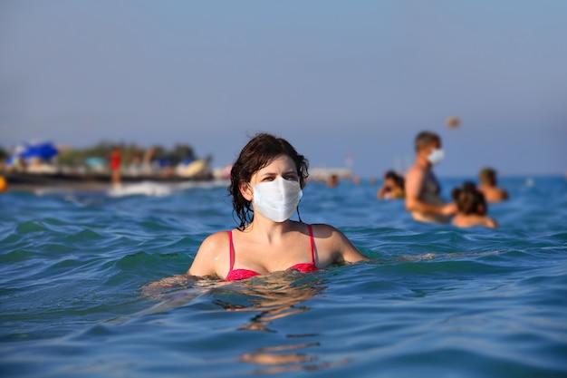Jovem mulher caucasiana se aquecendo no mar com uma máscara protetora.