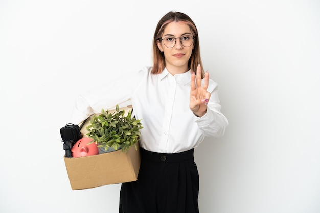 Jovem mulher caucasiana se mudando para uma nova casa entre caixas isoladas no fundo branco feliz e contando três com os dedos