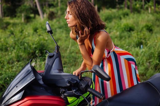 Jovem mulher caucasiana se olha no espelho da motocicleta em um campo tropical