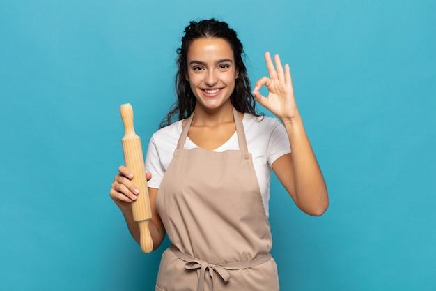 Jovem mulher caucasiana se sentindo feliz, relaxada e satisfeita, mostrando aprovação com um gesto de ok, sorrindo