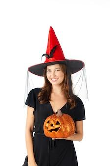 Jovem mulher caucasiana, segurando a cabeça de abóbora laranja em vestido preto e chapéu vermelho sobre fundo branco