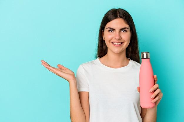 Jovem mulher caucasiana, segurando a garrafa de água isolada em um fundo azul, mostrando um espaço de cópia na palma da mão e segurando a outra mão na cintura.