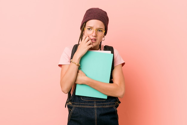 Jovem mulher caucasiana, segurando alguns cadernos, roer unhas, nervosas e muito ansiosas.