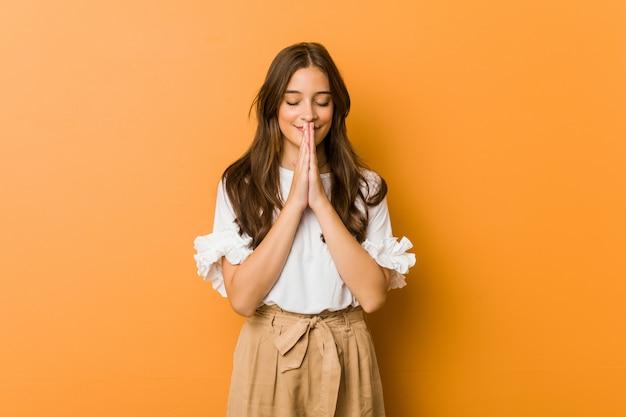 Jovem mulher caucasiana, segurando as mãos em rezar perto da boca, sente-se confiante.