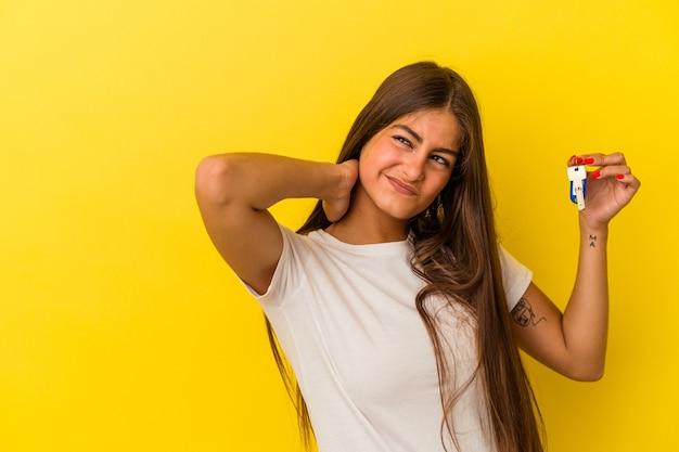 Jovem mulher caucasiana, segurando as teclas de uma casa isoladas no fundo amarelo, tocando a parte de trás da cabeça, pensando e fazendo uma escolha.