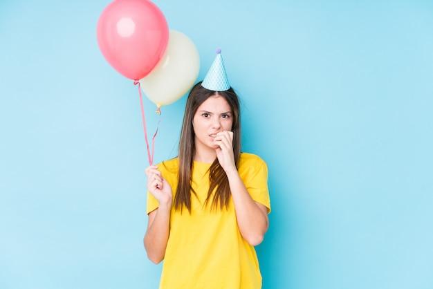 Jovem mulher caucasiana segurando balões com expressão preocupada