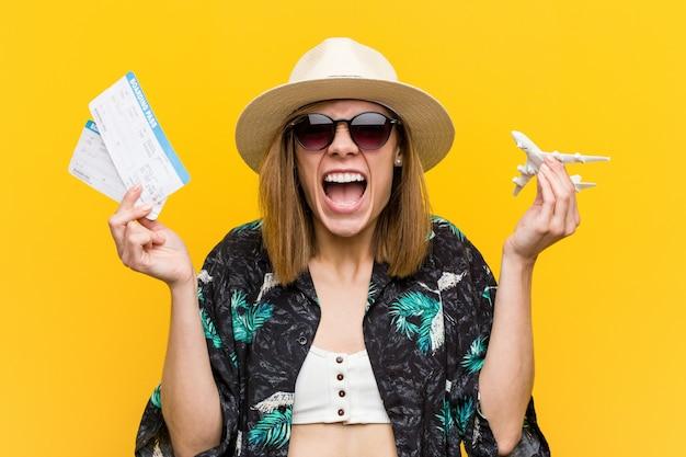 Jovem mulher caucasiana segurando bilhetes de avião muito felizes.