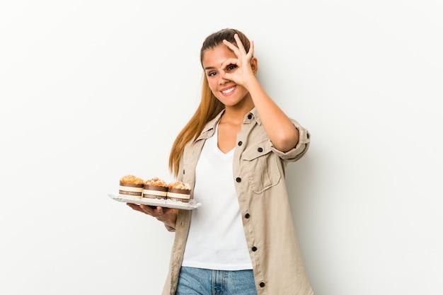 Jovem mulher caucasiana segurando bolos doces animado mantendo gesto bem no olho.
