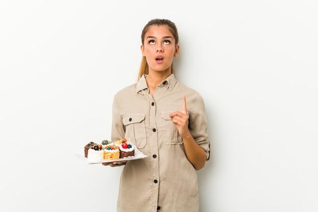Jovem mulher caucasiana, segurando bolos doces apontando para cima com a boca aberta.