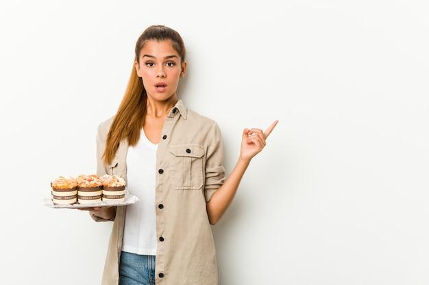 Jovem mulher caucasiana segurando bolos doces, apontando para o lado