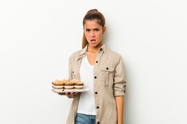 Jovem mulher caucasiana segurando bolos doces, gritando muito irritado e agressivo.