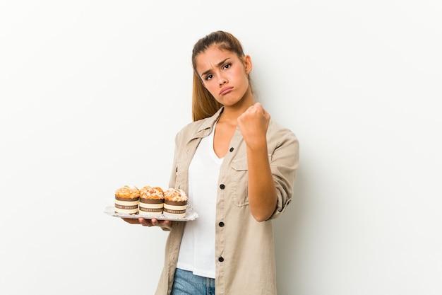 Jovem mulher caucasiana, segurando bolos doces, mostrando o punho para a câmera, expressão facial agressiva.