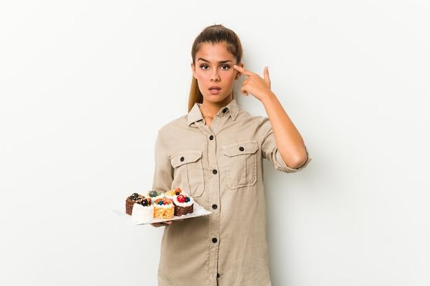Jovem mulher caucasiana segurando bolos doces, mostrando um gesto de decepção com o dedo indicador.