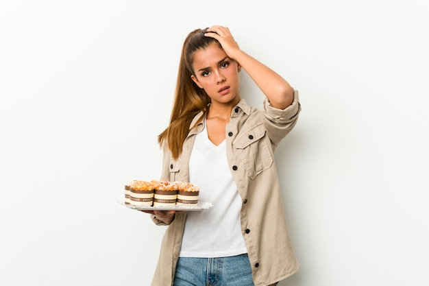 Jovem mulher caucasiana segurando bolos doces, sendo chocado, ela se lembrou de uma reunião importante.