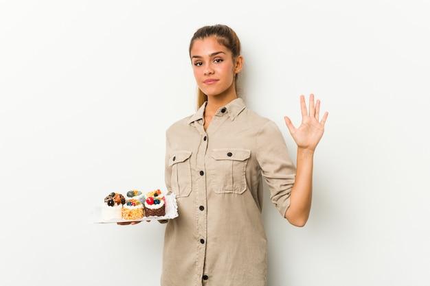 Jovem mulher caucasiana segurando bolos doces sorrindo alegre mostrando número cinco com os dedos.