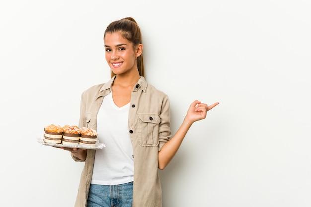 Jovem mulher caucasiana segurando bolos doces, sorrindo e apontando de lado