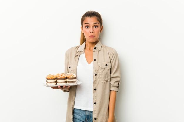 Jovem mulher caucasiana segurando bolos doces