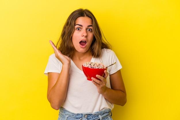 Jovem mulher caucasiana, segurando cereais isolados em fundo amarelo, surpresa e chocada.