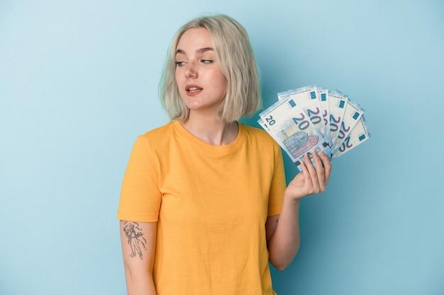 Jovem mulher caucasiana segurando contas isoladas em fundo azul parece de lado sorrindo, alegre e agradável.