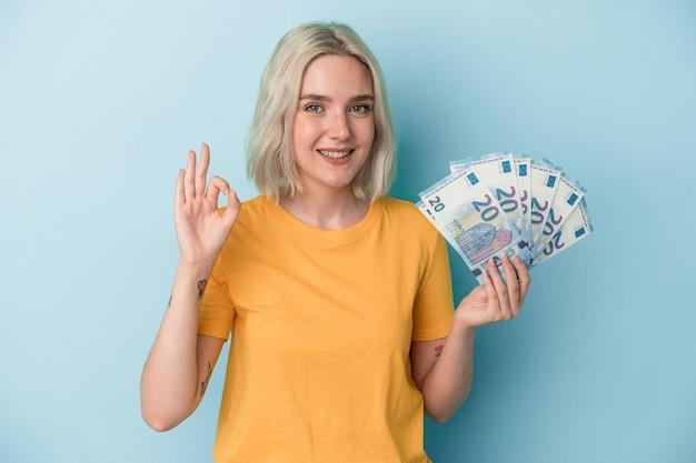 Jovem mulher caucasiana segurando contas isoladas em um fundo azul, alegre e confiante, mostrando um gesto ok.