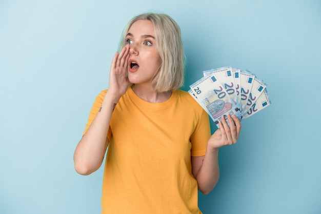 Jovem mulher caucasiana segurando contas isoladas em um fundo azul, gritando e segurando a palma da mão perto da boca aberta.