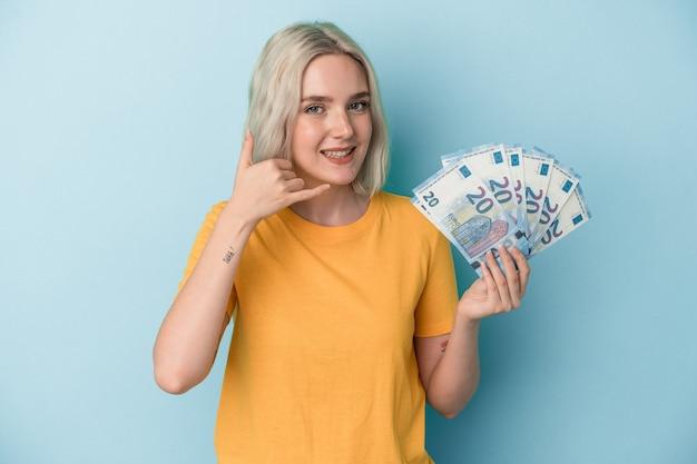 Jovem mulher caucasiana segurando contas isoladas em um fundo azul, mostrando um gesto de chamada de telefone móvel com os dedos.