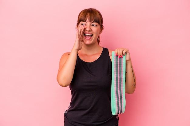 Jovem mulher caucasiana, segurando elásticos isolados em gritos de fundo rosa e segurando a palma da mão perto da boca aberta.