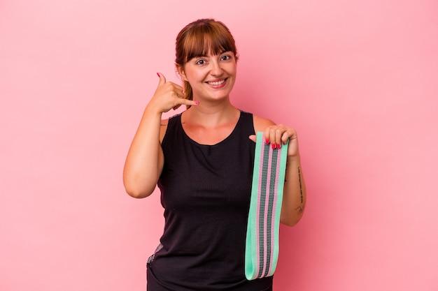 Jovem mulher caucasiana segurando elásticos isolados no fundo rosa, mostrando um gesto de chamada de telefone móvel com os dedos.