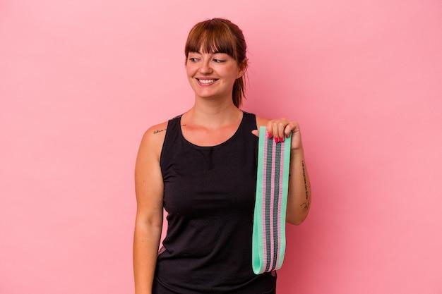 Jovem mulher caucasiana segurando elásticos isolados no fundo rosa parece de lado sorrindo, alegre e agradável.