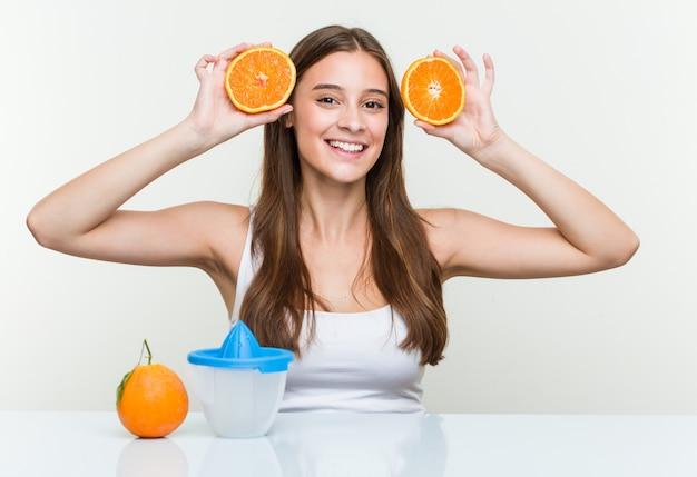 Jovem mulher caucasiana, segurando fazendo um suco de laranja