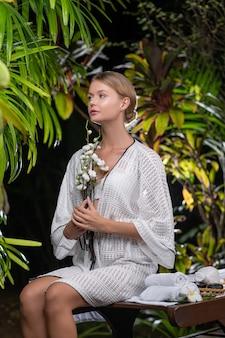 Jovem mulher caucasiana segurando flores brancas enquanto está sentado na mesa de massagem