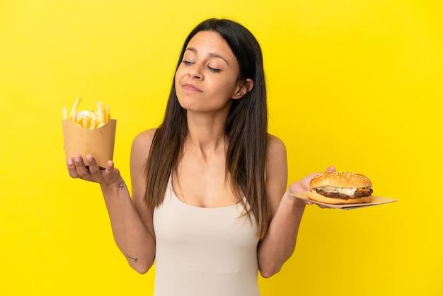 Jovem mulher caucasiana segurando hambúrguer e batatas fritas isoladas em um fundo amarelo
