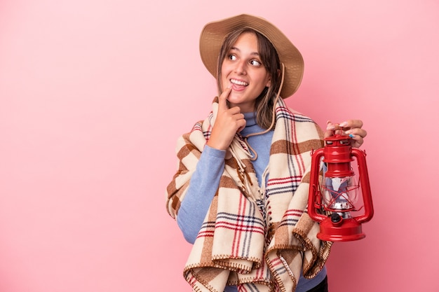 Jovem mulher caucasiana segurando lanterna vintage isolada no fundo rosa relaxada pensando em algo olhando para um espaço de cópia.