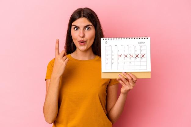 Jovem mulher caucasiana segurando o calendário isolado na parede rosa, tendo uma ótima ideia