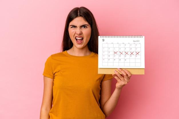 Jovem mulher caucasiana, segurando o calendário isolado no fundo rosa, gritando muito zangado e agressivo.