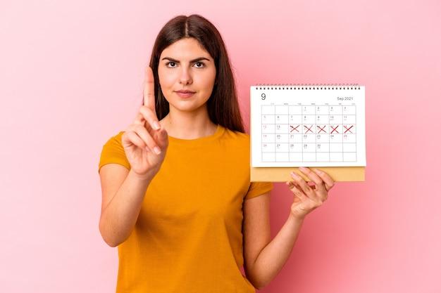 Jovem mulher caucasiana, segurando o calendário isolado no fundo rosa, mostrando o número um com o dedo.