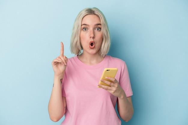 Jovem mulher caucasiana, segurando o celular isolado em um fundo azul, tendo uma ótima ideia, o conceito de criatividade.