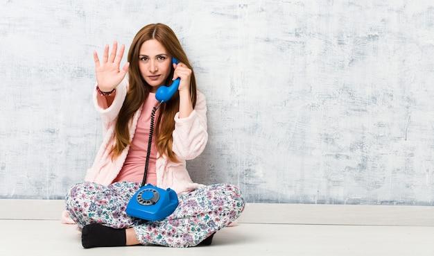 Jovem mulher caucasiana, segurando o telefone fixo em pé com a mão estendida, mostrando o sinal de stop, impedindo-o.