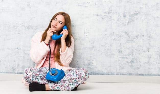 Jovem mulher caucasiana, segurando o telefone fixo, olhando de soslaio com expressão duvidosa e cética.