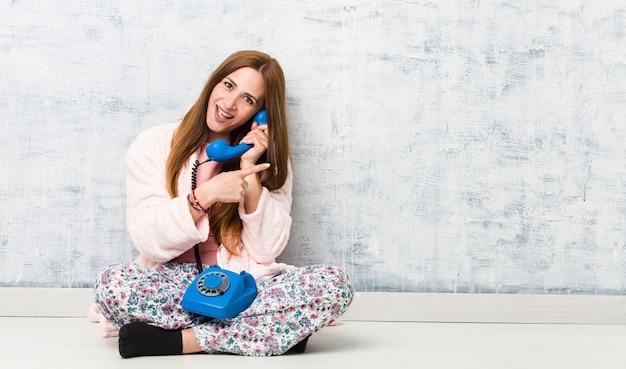 Jovem mulher caucasiana, segurando o telefone fixo sorrindo alegremente apontando com o dedo indicador.
